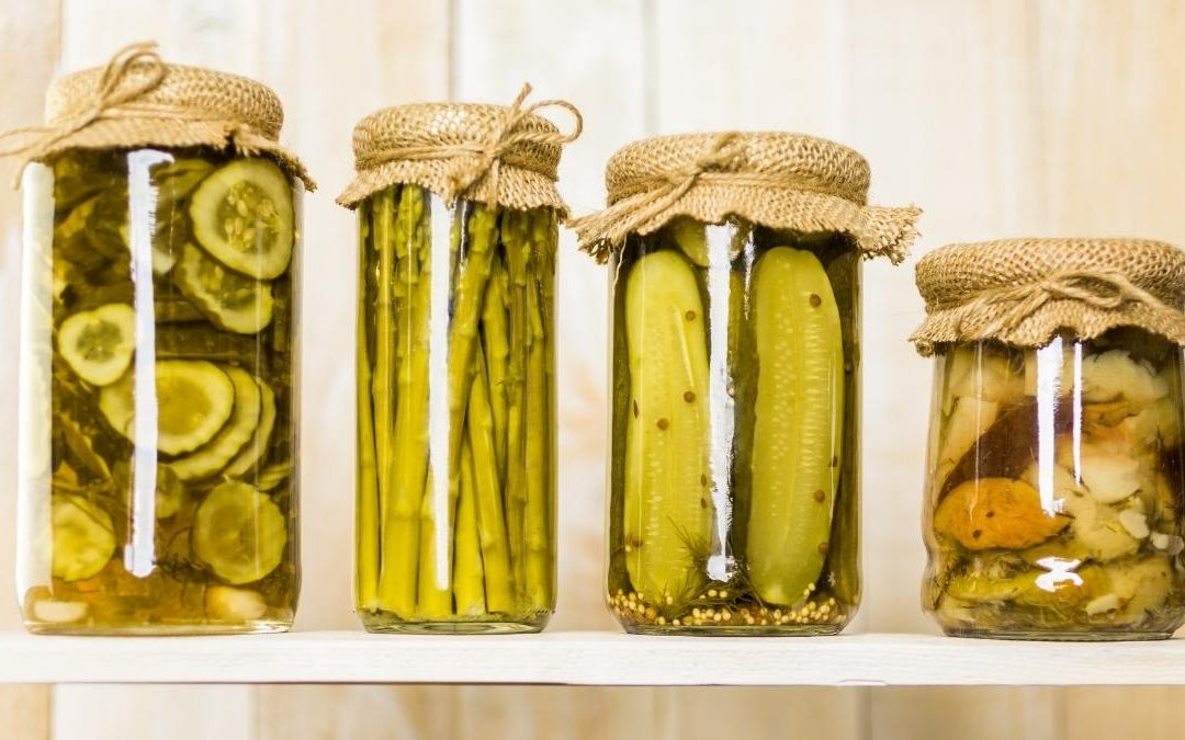 four jars containing canned vegetables