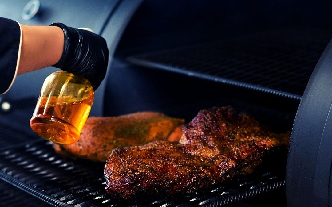 a man sprays seasoning to a meat on the smoker grill